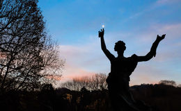 Statue dancing in the sky and point out at the moon. A silohuette of a statue with hands up in the sky at sunset Royalty Free Stock Image