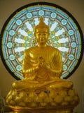 Statue de Bouddha avec le fond de fenêtre en verre teinté de forme de cercle Photographie stock libre de droits