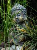 Statue de Bouddha de décoration peu dans un extérieur de jardin couvert d'herbe photos stock