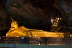 Statue de Bouddha d'or étendu en caverne Image stock