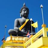 Statue de Bouddha montant dans le ciel bleu parmi les drapeaux thaïlandais et bouddhistes Photo libre de droits