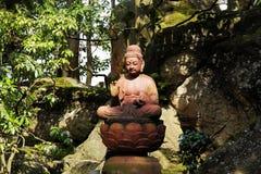 Statue de Bouddha Sakyamuni avec les arbres et la roche Photographie stock