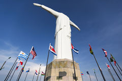 Statue de Cristo del Rey de Cali avec les drapeaux du monde et le ciel bleu, col Photo stock