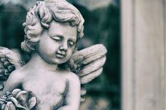 Statue de cupidon de beauté d'ange dans le jardin de vintage l'été Holdin Photographie stock