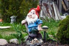 Statue de gnome avec le chapeau rouge dans le jardin Photographie stock libre de droits