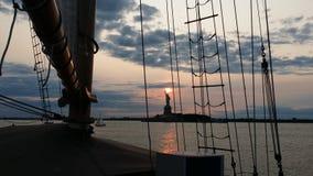 Statue de la liberté au coucher du soleil comme vu du bateau de tondeuse Photos stock