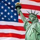 Statue de la liberté, du ciel ensoleillé et du drapeau des Etats-Unis Photo libre de droits