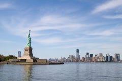 Statue de la liberté, et horizon de Manhattan derrière lui Photographie stock libre de droits