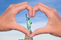 Statue de la liberté et mains formant un coeur, un amour de New York et un concept de voyage Photos stock