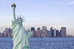Statue de la liberté et de New York d'horizon du dos dedans Photo libre de droits