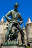 Statue de Lange Wapper devant le château en pierre à Anvers, Belgique Photos stock
