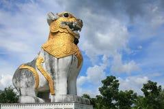 Statue de lion dans le type de la Birmanie contre le ciel bleu Photographie stock libre de droits