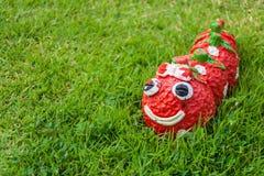 Statue de ver rouge de sourire dans le jardin Photographie stock libre de droits
