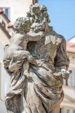 Statue de vieux prêtre avec le bébé à la vieille ville à Prague, Tchèque Repu Image stock