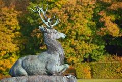 Statue of deer aginst autumn park trees backgrou. Statue of a deer in an autumn park Stock Photography