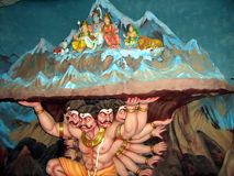 Statue of a Demon. With many hands and heads lifting a mountain with Lord Shiva Family Royalty Free Stock Photography