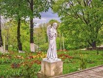 Statue des Engels im schönen Garten mit Blumen Lizenzfreies Stockbild