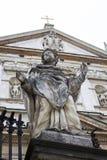 Statue des Heiligen auf dem Hintergrund einer mittelalterlichen Kirche mit einem Kreuz lizenzfreie stockbilder