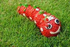 Statue des Lächeln-roten Wurmes im Gras Lizenzfreies Stockfoto