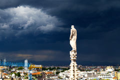 A statue of the Dome of Milan cathedral with the city view before the thunder. Stock Photography