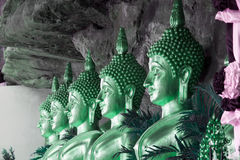Statue dorate di Buddha in una caverna al tempio buddista fotografia stock libera da diritti