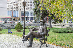 Statue in downtown Ploiesti. Metal statue of man sitting on a bench in downtown Ploiesti Royalty Free Stock Photos
