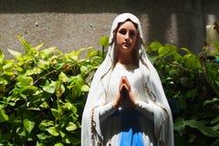 Statue du christianisme devant une vieille église Photos libres de droits