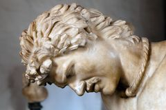 Statue of the Dying Gaul. The Dying Gaul, formerly known as the Dying Gladiator, is an ancient Roman marble copy of a lost bronze Hellenistic sculpture Stock Image