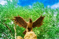 Statue of an eagle with open wings against a background of green trees and sky view from below stock images