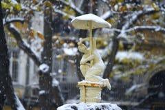 Statue einer Knabenfigur mit einem Regenschirm im Schnee Lizenzfreie Stockfotos