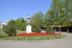 Statue eines Kollektivlandwirts auf einem Sockel Das Vermächtnis der sowjetischen Ära Ein Blumenbeet mit Tulpen und jungen Bäumen Lizenzfreie Stockfotos