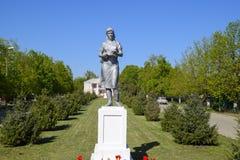 Statue eines Kollektivlandwirts auf einem Sockel Das Vermächtnis der sowjetischen Ära Ein Blumenbeet mit Tulpen und jungen Bäumen Lizenzfreies Stockbild