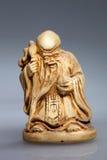 Statue eines Mönchs mit einem Stock Stockbild