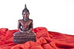 Statue en bois de Bouddha sur le tissu rouge Photographie stock