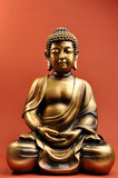 Statue en bronze de Bouddha sur le fond orange rouge Image stock