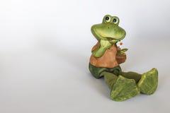 Statue en céramique de grenouille gaie avec la fleur Photographie stock libre de droits