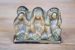 Statue en laiton de trois singes d'isolement sur la surface en bois Photos stock