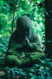 Statue en pierre de Bouddha dans le jardin envahi ombragé Photographie stock libre de droits