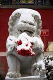Statue en pierre de lion dans la neige Photos libres de droits