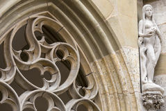 Statue of Eve and gothic rose window on the facade of St. Jakobs Kirche, Rothenburg ob der Tauber, Germany. Stock Photos