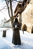 statue of a faceless monk with the hood raised and hands pointing up with a snowman on his hands. contrast and play of children royalty free stock photography