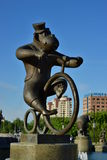 A statue featuring a monkey riding a circus bicycle Stock Image