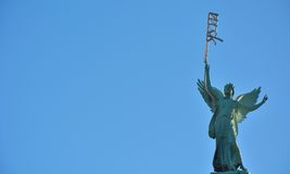 Statue of an female angel holding a strange neon light. In a clear blue sky Royalty Free Stock Photo