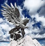 Statue of fish hunting eagle. Against cloudy sky stock images