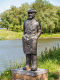 Statue of fisher on rampart of fortified town Woudrichem, Nether. Statue of salmon fisherman on rampart of fortified town Woudrichem and river Afgedamde Maas Royalty Free Stock Photos