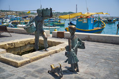The statue of the fishermen on the harbour of village Marsaxlokk Royalty Free Stock Image
