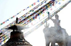 Statue and flags at Boudhanath Stupa Kathmandu. A statue of a woman with a sword riding an elephant and colorful flags hanging on ropes at Boudhanath Stupa stock images