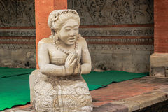 Statue with folded hands. In a temple in Bali Royalty Free Stock Image