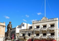 Old Paramount Cinema in Mosta, Malta. Statue in front of the Mosta Dome with the old Paramount cinema buildings to the rear around Rotunda Square in the town Royalty Free Stock Image
