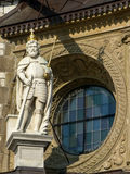 Statue in front of a window at Wawel Castle. An armored statue at Wawel Castle in Krakow, wearing a crown and holding a sword, in front of a circular window royalty free stock image